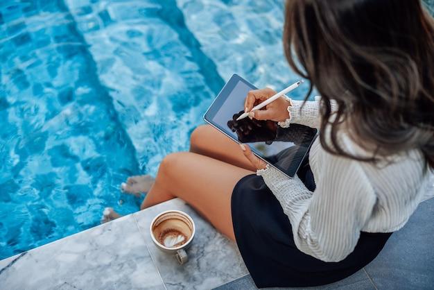 Jonge vrouwelijke student met golvende haren in formele kleding werkt op haar tablet rond het zwembad.