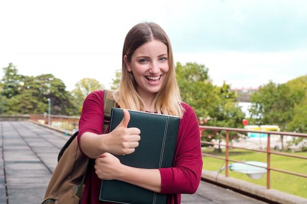 Jonge vrouwelijke student met mappen in college campus