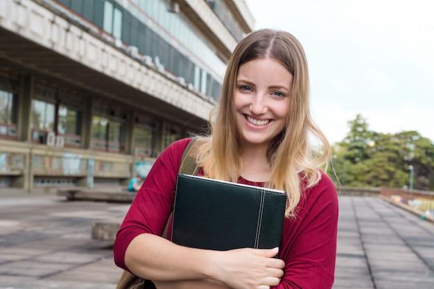 Jonge vrouwelijke student met mappen in college campus.