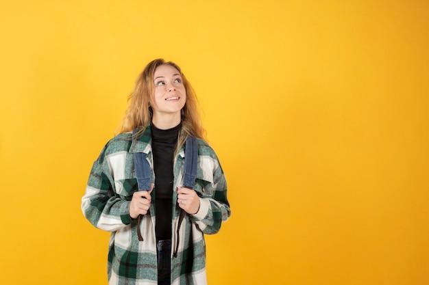Jonge vrouwelijke student met rugzak kijken naar kopie ruimte. middelbare school college onderwijs concept