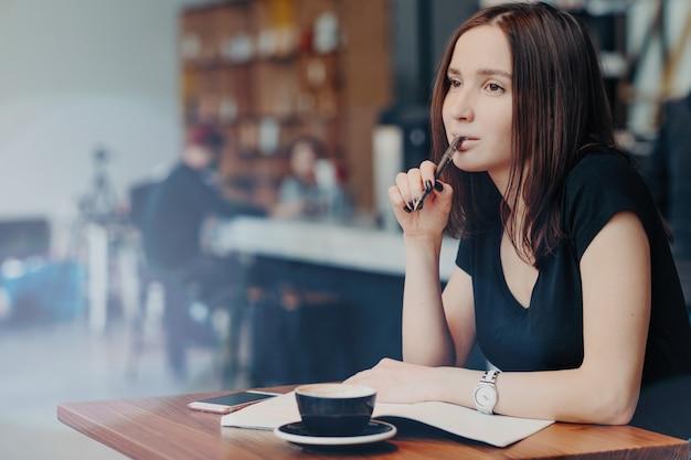 Jonge vrouwelijke student schrijft notities op voor rapport, werkt in coffeeshop, drinkt cappuccino