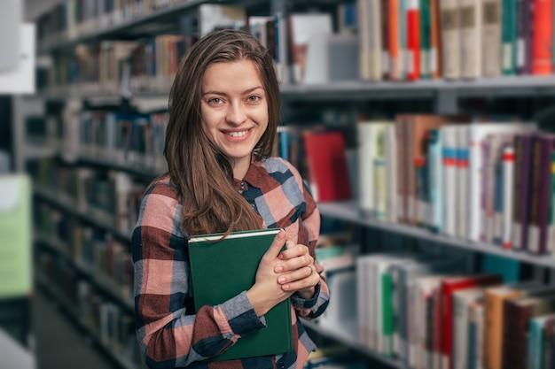 Jonge vrouwelijke studente die met boek in bibliotheek glimlachen