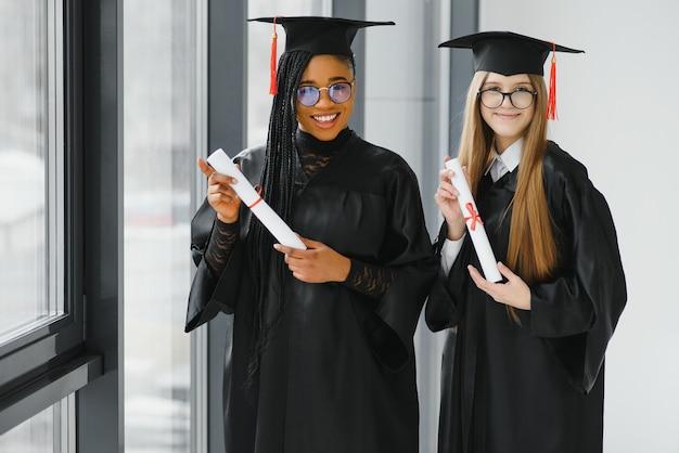 Jonge vrouwelijke studenten in gewaad die hun afstuderen vieren