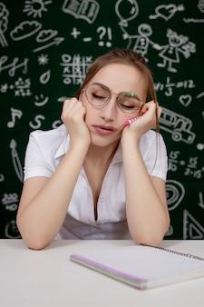 Jonge vrouwelijke studentenslaap in een klaslokaal