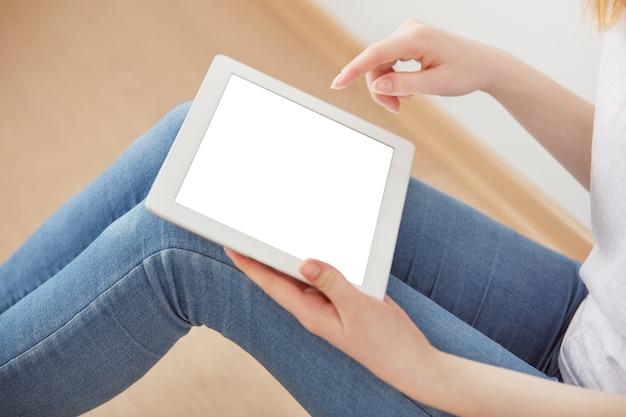 Jonge vrouwelijke studentenzitting in een universitaire recreatiezaal die touchpad gebruikt