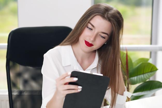 Jonge vrouwelijke studentenzitting in het bureau die problemen oplossen.