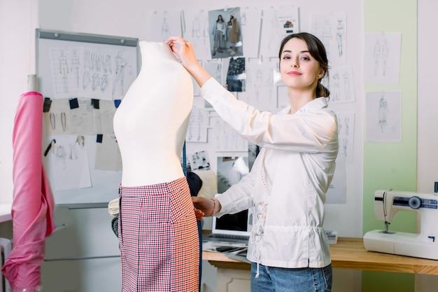 Jonge vrouwelijke stylist die broek op ledenpop met band meet. de manierontwerper die van de vrouw in studio werkt. fashion design mannequin meting concept.