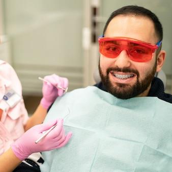 Jonge vrouwelijke tandarts arts en patiënt die bij camera bij tandkliniek glimlachen