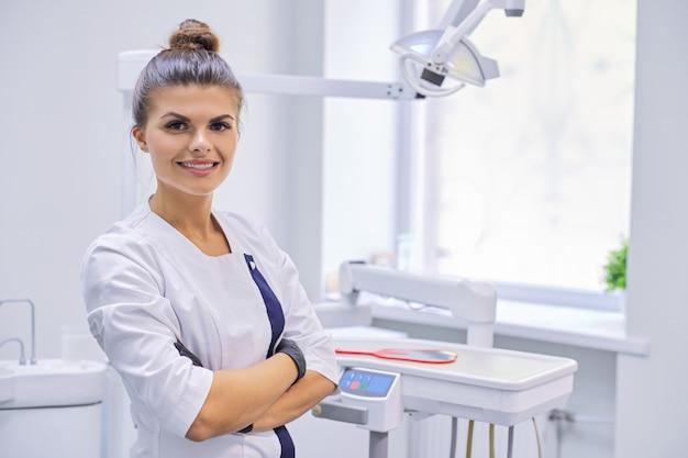 Jonge vrouwelijke tandarts in het kantoor