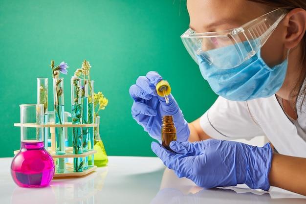Jonge vrouwelijke tech of wetenschapper laadt vloeibaar monster in fles met pipet.