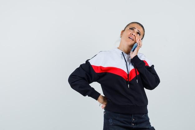 Jonge vrouwelijke telefoon bellen in kleurrijke sweatshirt en op zoek spraakzaam, vooraanzicht.