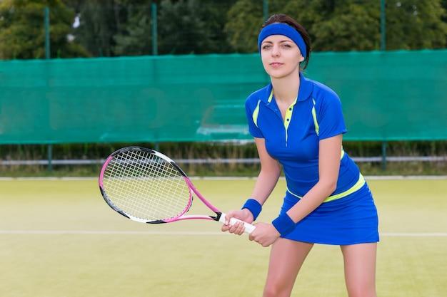 Jonge vrouwelijke tennisspeelster tijdens het spel het dragen van een sportkleding buiten in de zomer of de lente