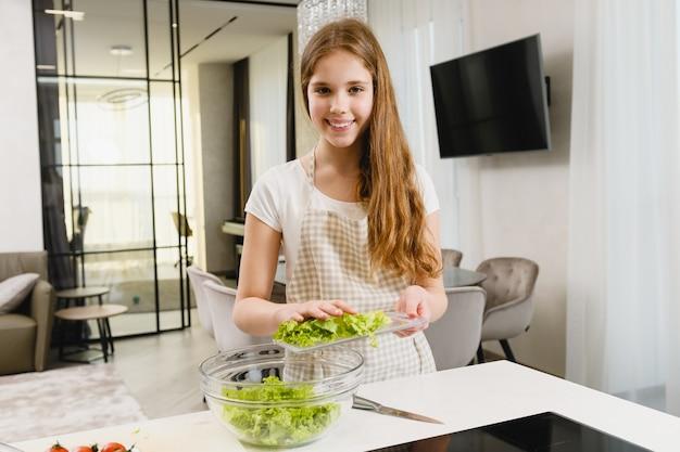 Jonge vrouwelijke tiener met een schort die verse salade kookt, ingrediënten snijdt en in een transparante kom aan een witte tafel doet