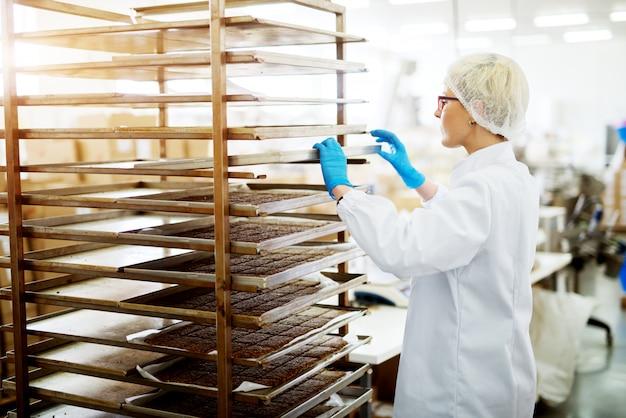 Jonge vrouwelijke toegewijde bakkerijarbeider in steriele doeken die blik met hete vers gebakken koekjes op een rek plaatsen om af te koelen.