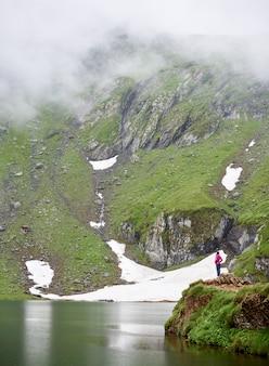 Jonge vrouwelijke toerist bewonderen schoonheid van de natuur voor grote geweldige groene rotsen