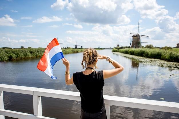 Jonge vrouwelijke toerist die achterover staat met nederlandse vlag en geniet van een prachtig uitzicht op het prachtige landschap met oude windmolens in nederland
