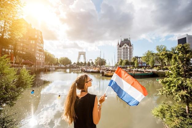 Jonge vrouwelijke toerist die achteruit staat met nederlandse vlag in de oude haven in de stad rotterdam