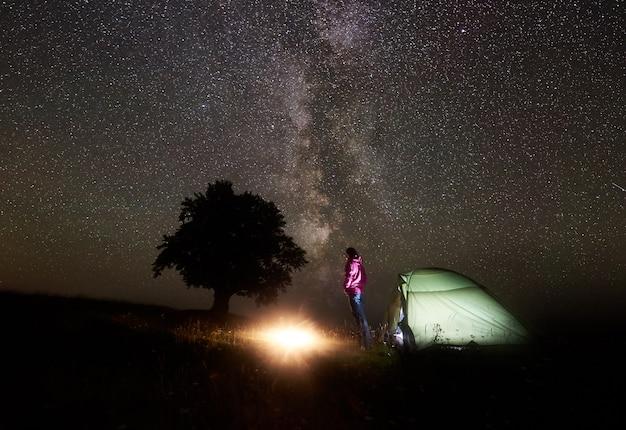 Jonge vrouwelijke toerist die dichtbij verlichte tent rusten, die in bergen bij nacht onder sterrige hemel kamperen