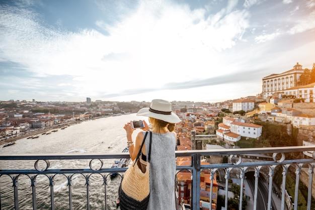 Jonge vrouwelijke toerist die geniet van een geweldig uitzicht op de oude stad die op de ijzeren brug staat tijdens de zonsondergang in de stad porto, portugal