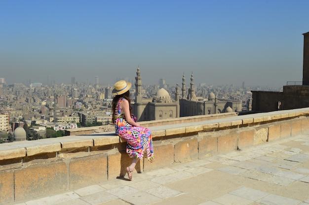 Jonge vrouwelijke toerist die geniet van het prachtige uitzicht op de oude citadel el-khalifa egypte