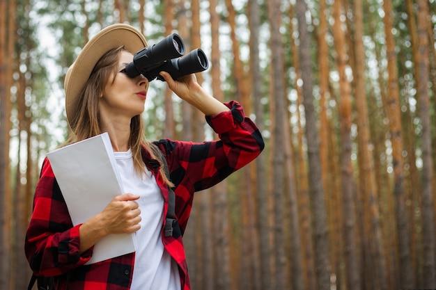 Jonge vrouwelijke toerist in een hoed en een rood geruit hemd houdt een kaart vast en kijkt door een verrekijker