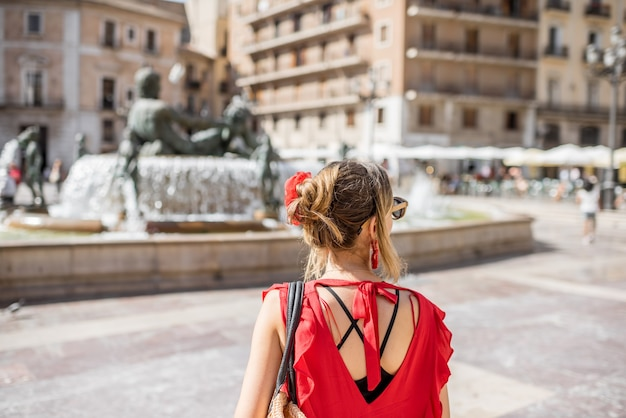 Jonge vrouwelijke toerist in rode jurk die achterover staat op het centrale plein in de stad valencia, spanje
