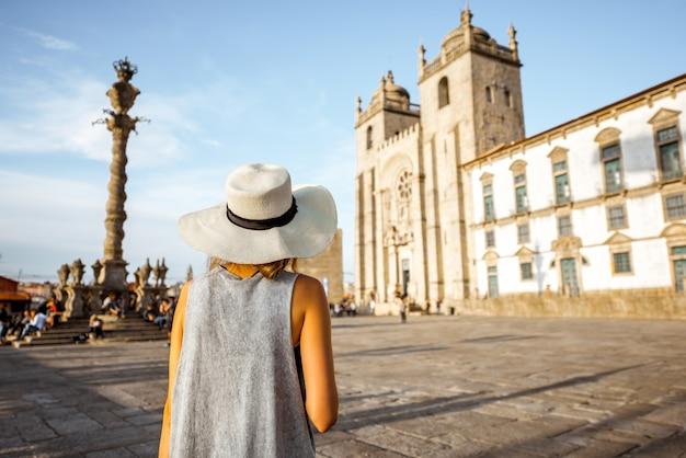 Jonge vrouwelijke toerist in zonnehoed die achter de belangrijkste kathedraal in de stad porto staat tijdens de zonsondergang in portugal