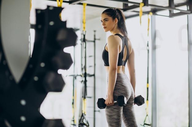 Jonge vrouwelijke trainer die traint in de sportschool