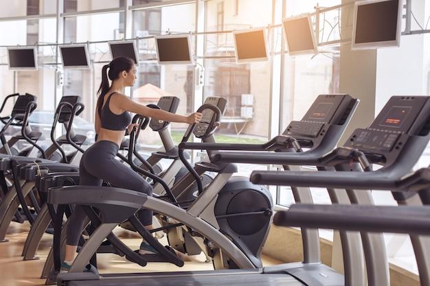 Jonge vrouwelijke training in de sportschool gezonde levensstijl elliptische trainer