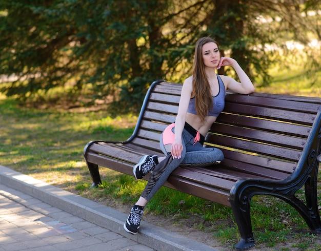 Jonge vrouwelijke training voor fitnesstraining in het park. gezonde jonge vrouw buiten opwarmen. ze strekt haar armen uit en kijkt weg.