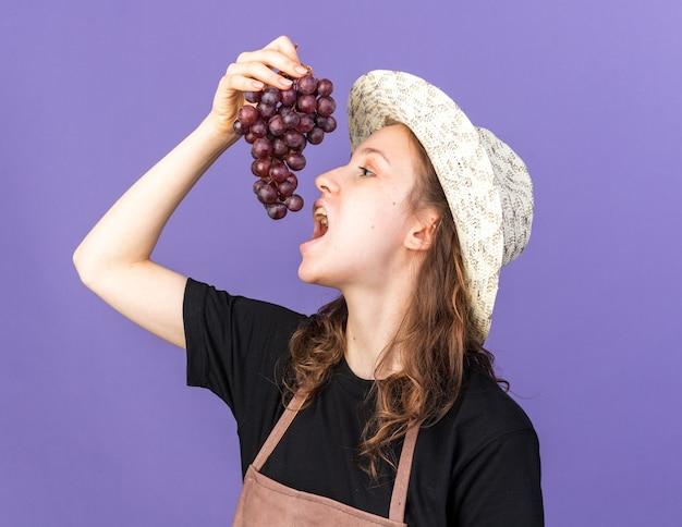 Jonge vrouwelijke tuinman die een tuinhoed draagt die druiven probeert
