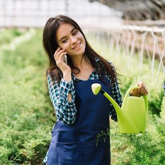 Jonge vrouwelijke tuinman die op de telefoon spreekt