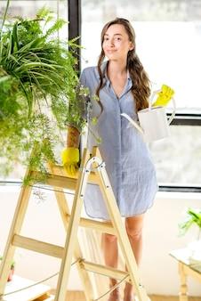 Jonge vrouwelijke tuinman die voor planten zorgt die met een gieter op de ladder in de oranjerie staan