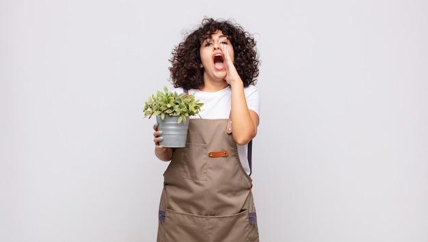 Jonge vrouwelijke tuinman die zich gelukkig, opgewonden en positief voelt, een grote schreeuw geeft met de handen naast de mond, roept