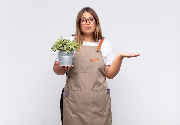 Jonge vrouwelijke tuinman die zich verward en verward voelt, twijfelt, weegt of verschillende opties kiest met grappige uitdrukking