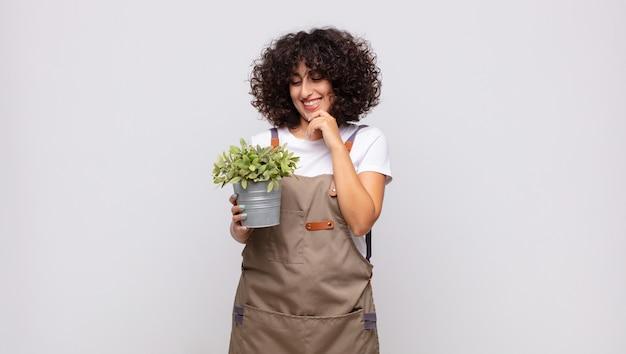 Jonge vrouwelijke tuinman glimlachend met een gelukkige, zelfverzekerde uitdrukking met de hand op de kin, zich afvragend en opzij kijkend