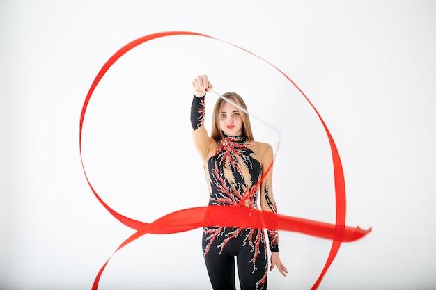 Jonge vrouwelijke turner met rood lint op witte achtergrond