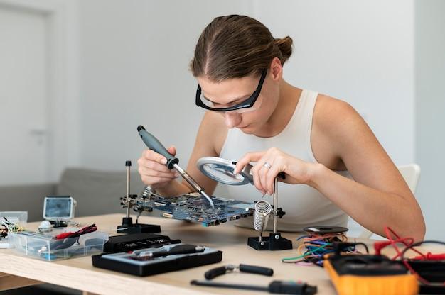 Jonge vrouwelijke uitvinder die in haar werkplaats creëert