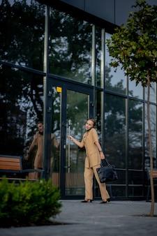 Jonge vrouwelijke uitvoerende macht die zich buiten kantoorgebouw bevindt dat op celtelefoon spreekt. caucacian zakenvrouw die een telefoongesprek voert terwijl hij tegen een hoofdkantoor staat.