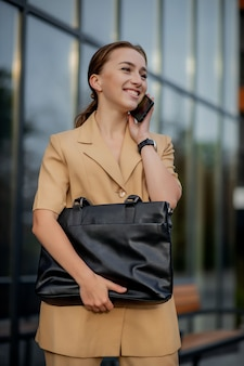 Jonge vrouwelijke uitvoerende macht die zich buiten kantoorgebouw bevindt dat op celtelefoon spreekt
