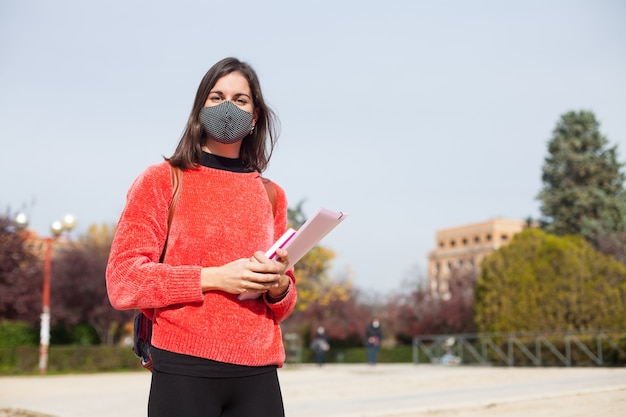 Jonge vrouwelijke universiteitsstudent die buiten masker draagt tijdens coronavirus-tijden