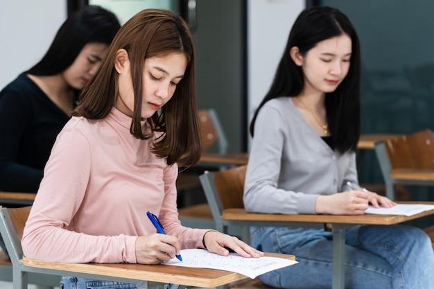 Jonge vrouwelijke universiteitsstudenten concentreren zich op het doen van examen in de klas. meisjesstudenten schrijven serieus de oefening van de examens in de klas.