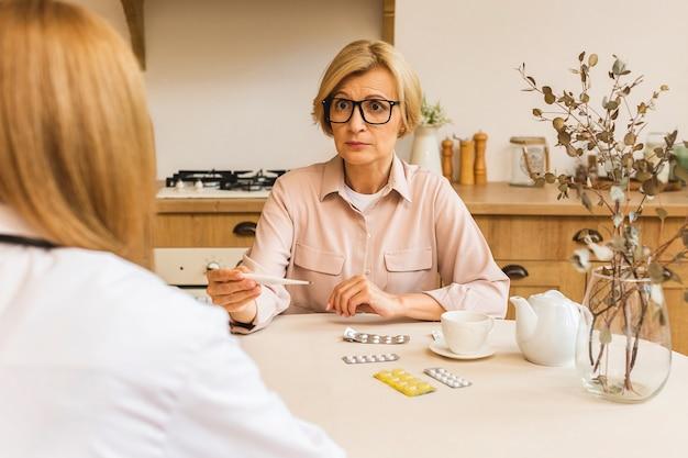Jonge vrouwelijke verpleegster biedt medische zorg, helpt senior volwassen vrouw ondersteunen bij medisch bezoek aan thuiszorg, lady verzorger arts geeft empathie en moedigt gepensioneerde patiënt in de keuken aan.