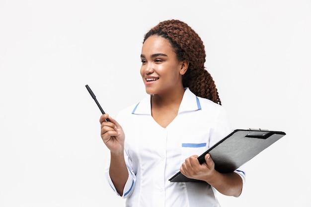 Jonge vrouwelijke verpleegster die medisch casusrapport schrijft dat tegen een witte muur wordt geïsoleerd