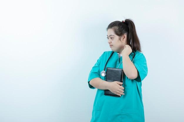 Jonge vrouwelijke verpleegster met de blocnote van de stethoscoopholding tegen witte muur.