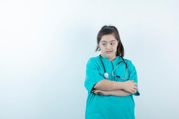 Jonge vrouwelijke verpleegster met stethoscoop poseren met gekruiste armen tegen witte muur.