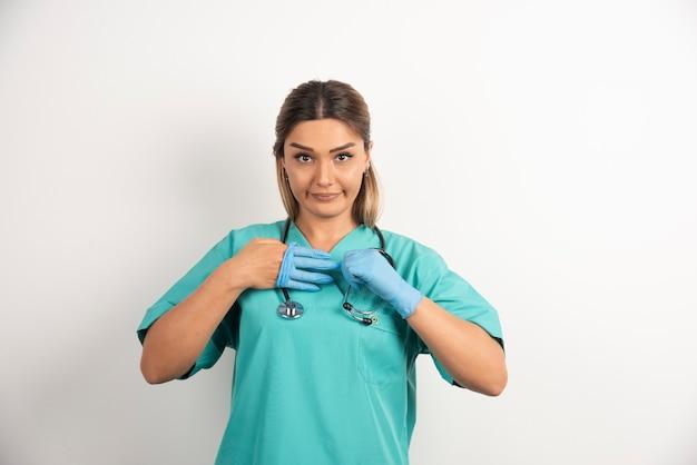 Jonge vrouwelijke verpleegster poseren gekleed in medische jurk.