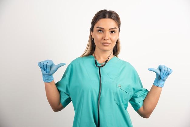 Jonge vrouwelijke verpleegster wijzend naar zichzelf op witte achtergrond