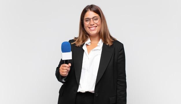 Jonge vrouwelijke verslaggever die blij en aangenaam verrast kijkt, opgewonden met een gefascineerde en geschokte uitdrukking