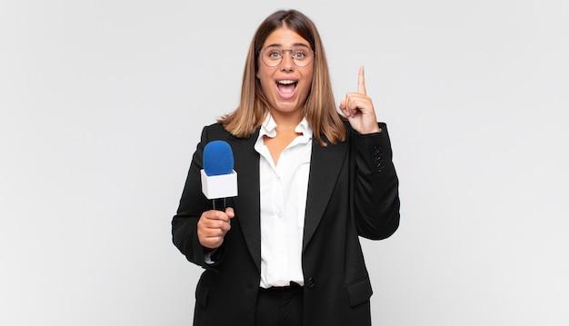 Jonge vrouwelijke verslaggever die zich als een gelukkig en opgewonden genie voelt na het realiseren van een idee, vrolijk de vinger opheffend, eureka!